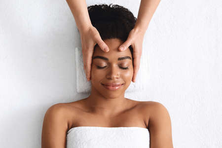 Top view of relaxed black lady getting healing head massage on white background. Smiling african american young woman with closed eyes enjoying relaxing procedure at spa, view above