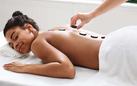 Joyful young black woman having hot stone massage at modern spa, side view. Spa female therapist placing black stones on relaxed young african american lady back, healing massage at spa salon