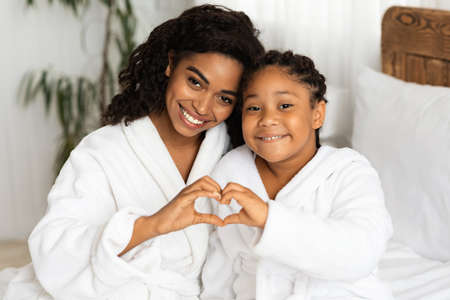 Happy Black Mom And Daughter In Bathrobes Making Heart Sign Form Hands, Connecting Their Arms, Having Fun And Bonding At Home, Relaxing On Bed Together After Bath, Smiling At Camera, Closeup