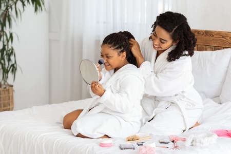 Beauty Day. Young African Mother And Daughter In Bathrobes Having Fun After Bath, Mom Braiding Childs Hair While Cute Girl Holding Mirror And Playing With Makeup Brush While Sitting On Bed In Bedroom