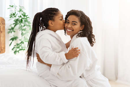 Happy Mothers Day. Adorable Black Little Girl Kissing Her Mom At Home, Family Wearing Bathrobes While Relaxing In Bedroom After Domestic Spa Treatments, Happy Mum Looking At Camera, Copy Space Archivio Fotografico