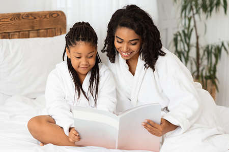 Happy african american mother and daughter in white bathrobes sitting on bed reading glamour magazine, enjoying beauty spa day at home, having fun together, relaxing in bedroom, copy space