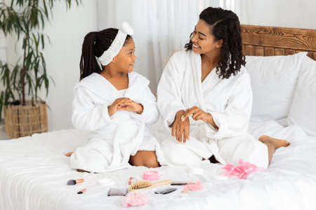 Little Black Girl And Her Mother Wearing Bathrobes Doing Beauty Treatments At Home, Applying Moisturising Cream On Hands, Sitting On Bed With Lots Of Cosmetics Around, Having Domestic Spa Day Archivio Fotografico
