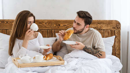 Free time, quarantine and romantic breakfast in bed. Happy millennial couple with tray with coffee and croissants eats in modern bedroom interior at home or hotel during covid-19 or honeymoon