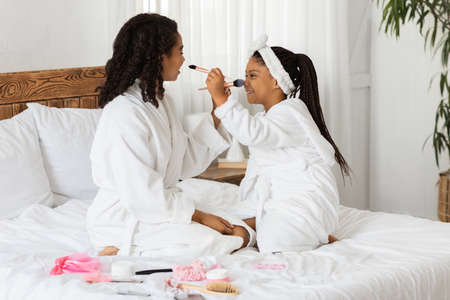 Cheerful African Mom And Little Daughter In Bathrobes Having Fun Together, Playing With Makeup Brushes While Making Beauty Salon At Home, Sitting On Bed, Enjoying Time With Each Other, Copy Space
