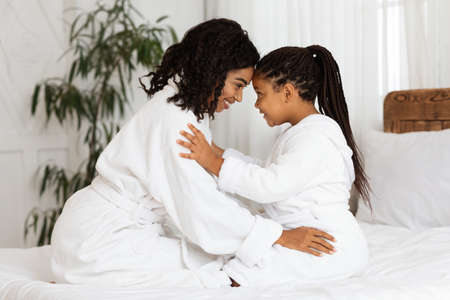 Loving Black Mother Bonding With Her Little Daughter On Bed At Home, Wearing Bathrobes, Relaxing Together After Domestic Beauty Spa, Touching Foreheads And Looking At Each Other With Love, Side View Archivio Fotografico