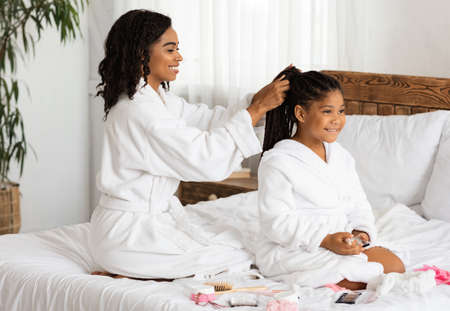 Home Beauty Salon. Loving Black Mom Braiding Hair To Her Cute Little Daughter, Having Domestic Spa Day, Wearing Bathrobes While Relaxing Together On Bed, Having Fun And Enjoying Time With Each Other
