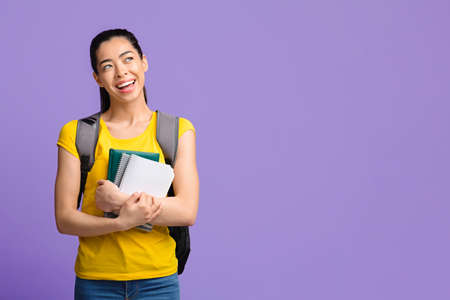 Dreamy korean female college student with backpack and workbooks looking away at copy space over purple studio background, thinking about education program offer and study abroad, copy space