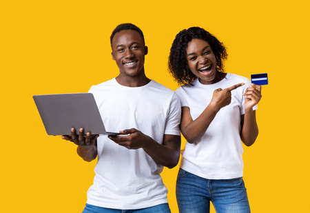 Online banking and e-commerce. Happy african-american man and woman pointing at credit card and working on laptop on yellow studio background. Black couple making purchases online, using laptop