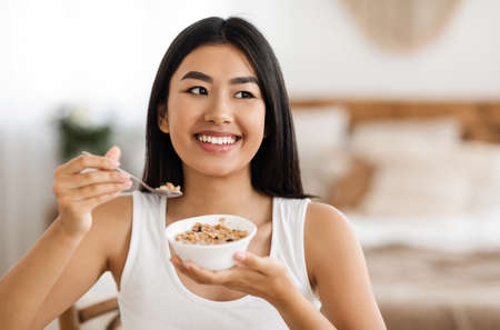 Happy asian woman holding bowl with homemade granola at bedroom. Healthy beautiful lady eating nutritive oatmeal at home, holding plate and spoon, smiling and looking at copy space, having breakfast Stock Photo