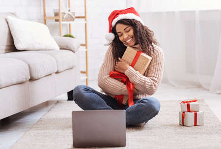 Christmas And New Year Presents. Happy Black Lady Holding And Embracing Gift Box, Sitting On The Floor At Home In Living Room With Laptop Computer, Celebrating Online, Making Video Conference