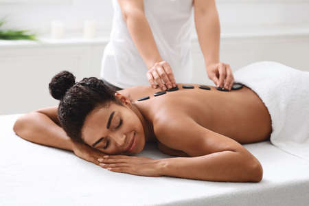Relaxed african american woman having hot stone massage at modern spa, side view. Female massage therapist placing black stones on young black lady back, healing massage at luxury spa salon 写真素材
