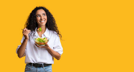 Cheerful Woman Eating Vegetable Salad From Bowl And Looking At Copy Space On Yellow Background, YoungLady Enjoying Heathy Nutrition And Organic Food, Having Vegetarian Meal For Lunch, Panorama Banco de Imagens