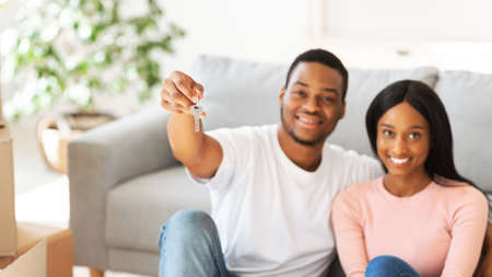 Positive black guy showing house key and his wife smiling in new home, selective focus. Millennial African American couple happy to move to bigger apartment, space for text