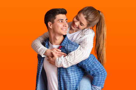 Have fun together and free time of couple in love at date. Happy guy in casual holds young cheerful woman on his back and looks at each other, isolated on orange background, free space, studio shot