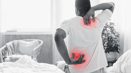 Back And Neck Pain. Black Man Suffering Backache Touching Aching Neck And Back Sitting In Bed At Home In The Morning. Spine Health Problem Concept. Black-And-White, Panorama With Copy Space, Back-View