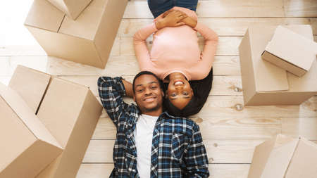 Black young woman with her handsome husband lying among cardboard boxes on floor of their new home, top view. Happy African American couple taking break on relocation day. Panorama Banco de Imagens