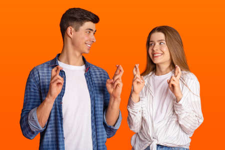 Luck and superstition. Cheerful millennial couple gesturing crossing fingers in hope, anticipate something with faithful expressions and look at each other, isolated on orange background, studio shot