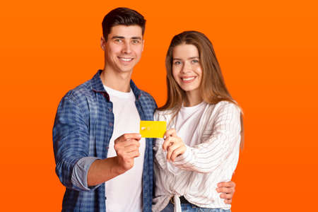 Online shopping, modern lifestyle and quick payment. Smiling guy and female in casual clothes holds credit card together and looking at camera, isolated on orange background, studio shot, free space