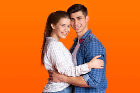 Beautiful happy couple in love and real feelings in relationships. Portrait of millennial cheerful family in casual clothes, man and woman hugging and looking at camera, isolated on orange background
