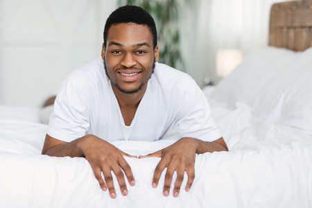 Good Morning. Positive African American Man Lying On Stomach In Bed Smiling To Camera Posing Waking Up In Bedroom At Home. Domestic Lifestyle, Recreation, Weekend Concept Zdjęcie Seryjne