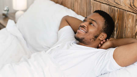 Happy Wellslept African American Guy Lying Awake In Bed In The Morning In Bedroom At Home. Good Morning, Awakening, Weekend Relaxation And Rest Concept. Panorama