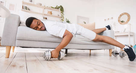 Exhausted African American Guy Sleeping Holding Dumbbell Lying On Sofa After Exhausting Workout Training At Home. Fitness Beginner Difficulties, Sporty Lifestyle. Panorama Stock fotó