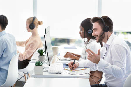 Team of customer service representatives assisting clients, resolving technical issues or selling products at modern call centre. Group of hotline operators working in telemarketing
