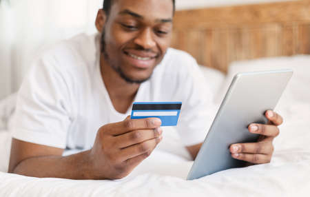 African American Man Shopping Online Using Digital Tablet And Credit Card Lying In Bed At Home. Internet Shop Offers And Sales, E-Commerce Concept. Selective Focus, Shallow Depth