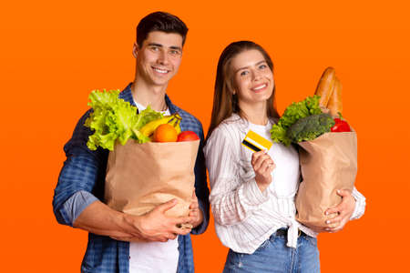Modern shopping and contactless payment with modern technology. Happy young man and woman holding paper bags with groceries and credit card, isolated on orange background, studio shot, free space
