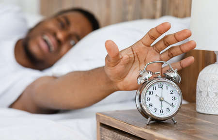 Early Awakening. Stressed African American Guy Turning Off Alarm Clock Waking Up Early In The Morning Lying In Bed At Home. Time To Wake Up Concept. Selective Focus, Shallow Depth