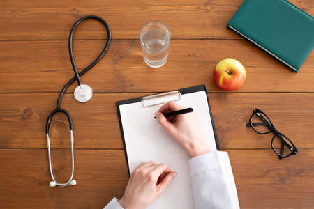 Recommendations and prescription from doctor. Woman in white coat writes on tablet at workplace, on wooden table with stethoscope, glasses, apple and glass of water, top view, copy space, cropped Imagens