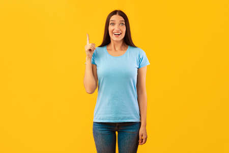 Great Idea Concept. Young Funny Woman Pointing Finger Up. Excited Lady Knows Answer, Got Solution To Problem, Having Aha Moment Or Inspiration, Isolated On Yellow Studio Background. Wow, Eureka Imagens