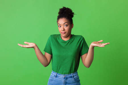 Who Knows. Portrait of Funny Young Black Woman Shrugging Shoulders Looking At Camera Posing Over Green Background. Studio Shot. Puzzled lady is clueless. Im sorry, exuse me, cant decide