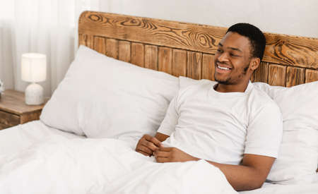 Happy Relaxed African American Man Watching TV Sitting In Bed In Bedroom At Home. Domestic Lifestyle, Weekend Relaxation And Rest Concept. Blank Space For Text