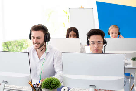 Multinational customer service representatives in headsets working behind their PC monitors at call centre. Group of hotline operators communicating with clients, promoting products or making poll