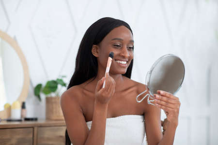 Morning ritual for beauty care. Happy millennial attractive african american woman wrapped in towel after shower applying makeup on face with brush and looking in mirror in bedroom, free space Reklamní fotografie