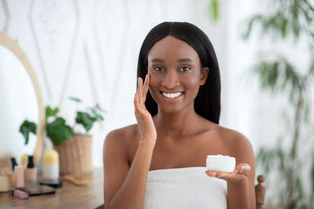 Beauty salon at home, skin care and self-isolation during covid-19 pandemic. Cheerful beautiful young african american lady in towel, applies cream to face in modern bedroom blurred interior