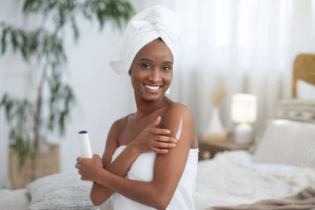 Beauty care, spa day at home and free time. Focus on smiling young african american woman in towel, applies body moisturizer after shower holds bottle of cosmetic in modern bedroom interior, blurred