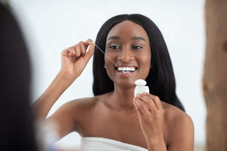 Morning dental care after shower at home and everyday routine procedure. Cheerful millennial african american lady wrapped in towel with perfect smile flossing teeth in bedroom interior, free space