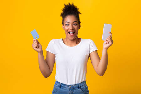 Mobile Shopping App. Portrait Of Joyful Black Lady Holding Credit Card And Cellphone Posing Standing Over Yellow Studio Background. Excited African American Woman Making Online Purchase
