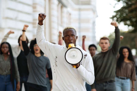 African american man with megaphone leading international group of protestors on the street, raising fist up, chanting slogans. Leader of strikers with loudspeaker yelling demands to government