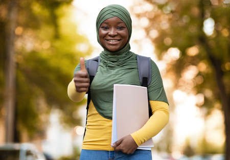 Black Muslim Female Student In Hijab Posing Outdoors, Showing Thumb Up Gesture At Camera, Carrying Backpack And Workbooks, Cheerful College Lady In Headscarf Walking On Autumn Street, Copy Space
