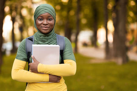 Smiling black student lady in hijab standing outdoors with workbooks, carrying backpack and posing to camera, islamic female having free time at campus park, copy space