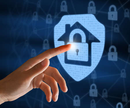 Home Security System And Protection Concept. Female hand touching hologram of locked house icon with finger. Modern Technology For Surveillance And Remote Control. Internet Of Things And Safety 免版税图像