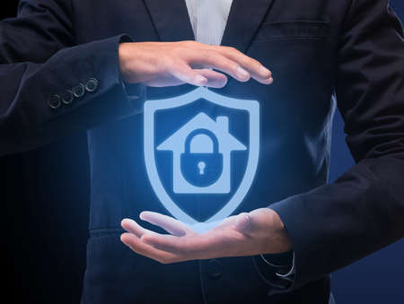Home Security System And Protection Concept. Man in suit holding hologram of locked house icon in hands. Modern Technology For Surveillance And Remote Control. Internet Of Things And Safety