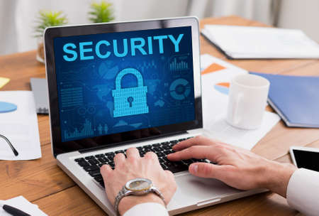 Data Protection And Privacy Concept. Over the shoulder view of businessman typing on laptop keyboard, padlock icon with security system on the screen. Protect information from fraud and online crime