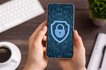 Data Protection, Mobile Application Concept. Above top view of woman holding and using smartphone, padlock icon with binary code on the screen. Personal information, online cyber security