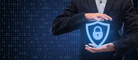 Internet Privacy, Technology And Data Protection Concept. Closeup of businessman holding virtual security shield hologram with padlock. Panorama, banner with binary code in the background