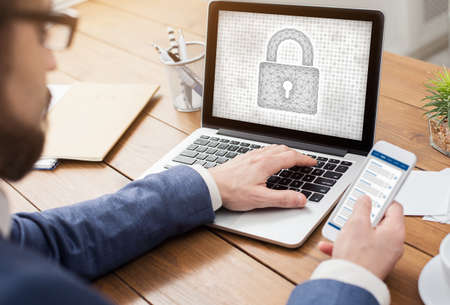 Protect Your Personal Information. Over the shoulder view of man typing on laptop keyboard, holding mobile phone, padlock icon on the computer screen. Data And Cyber Security Concept. 免版税图像